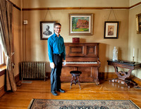 Will Stoutamire, Director of the Frank House Museum in front of the piano used for music performances hence the scars in the floor finish caused by moving the piano out into the hall.
