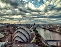 "On the left the Clyde Auditorium, familiarly known as ""The Armadillo"", is a concert venue in Glasgow, Scotland. The building sits on the site of the now infilled Queen's Dock on the River Clyde."