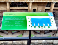 Marker identifying the late 19th century carvings of Roman Emperors and Governors of Roman Britain on the terrace overlooking the Great Bath.
