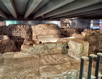 A general view of the crypt.  Medieval cellars in foreground and in the background the original smooth stone flagged cold room floor of the Roman baths are visible.