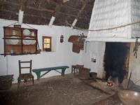 Interior of the Shannon Farmhouse at Bunratty Folk Park; you can see the glow of the peat fire on the hearth.