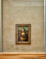 Leonardo da Vinci's Mona Lisa, a rather small painting, behind protective glass, surrounded by hordes of tourists in the Louvre.