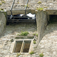 The Blarney Stone is the rectangular rock with metal straps holding it to the bottom of the parapet.